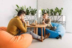 voksne spiller skak mens de slapper af i sækkestolen